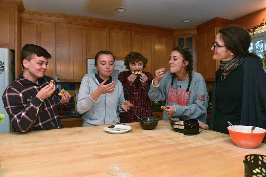 From right, Caroline Barrett makes peanut butter waffles with her kids Zoe, Elliot, Lucy and their friend Quinn in her home on Thursday, March 19, 2020 in Delmar, N.Y. (Lori Van Buren/Times Union) Photo: Lori Van Buren, Albany Times Union / 40049030A
