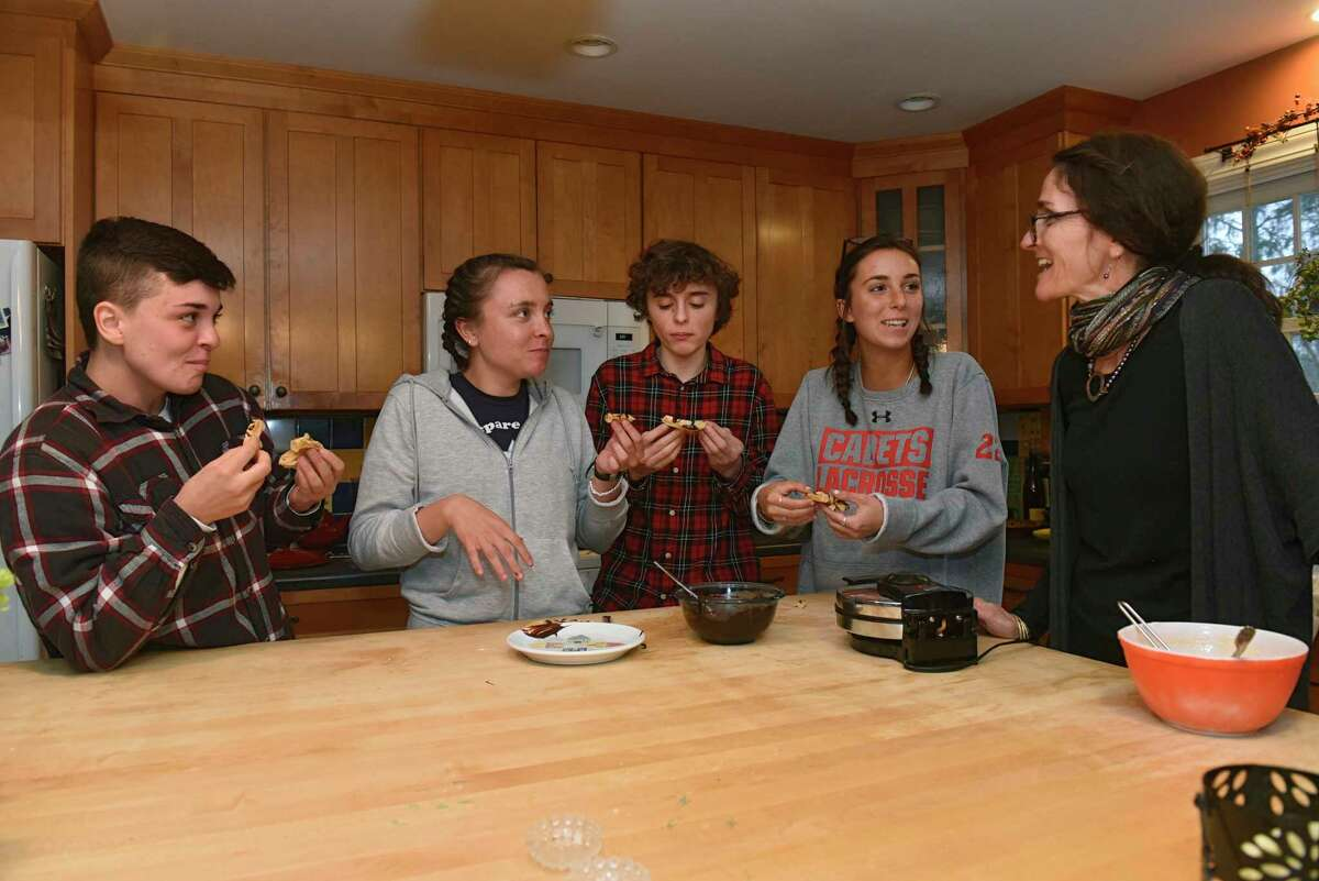 From right, Caroline Barrett makes peanut butter waffles with her kids Zoe, Elliot, Lucy and their friend Quinn in her home on Thursday, March 19, 2020 in Delmar, N.Y. (Lori Van Buren/Times Union)