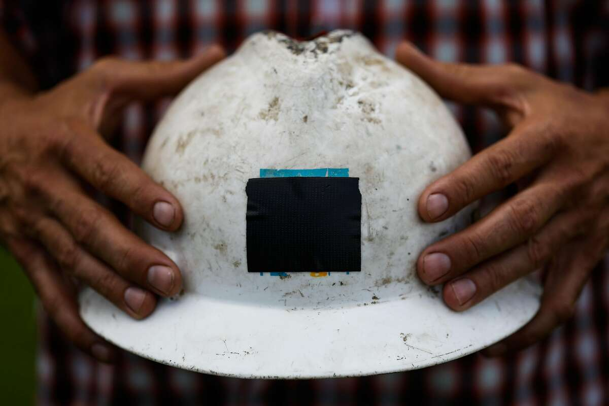 Luke Bellefeuille holds his PG&E hard hat which he covered with black tape so that people wouldn't confuse him for a PG&E worker while he helps clear property for friends in Paradise, California, on Thursday, May 23, 2019. Luke works for PG&E and lost his house in the Camp Fire. He decided to take a leave of absence to help family and friends with property damage.