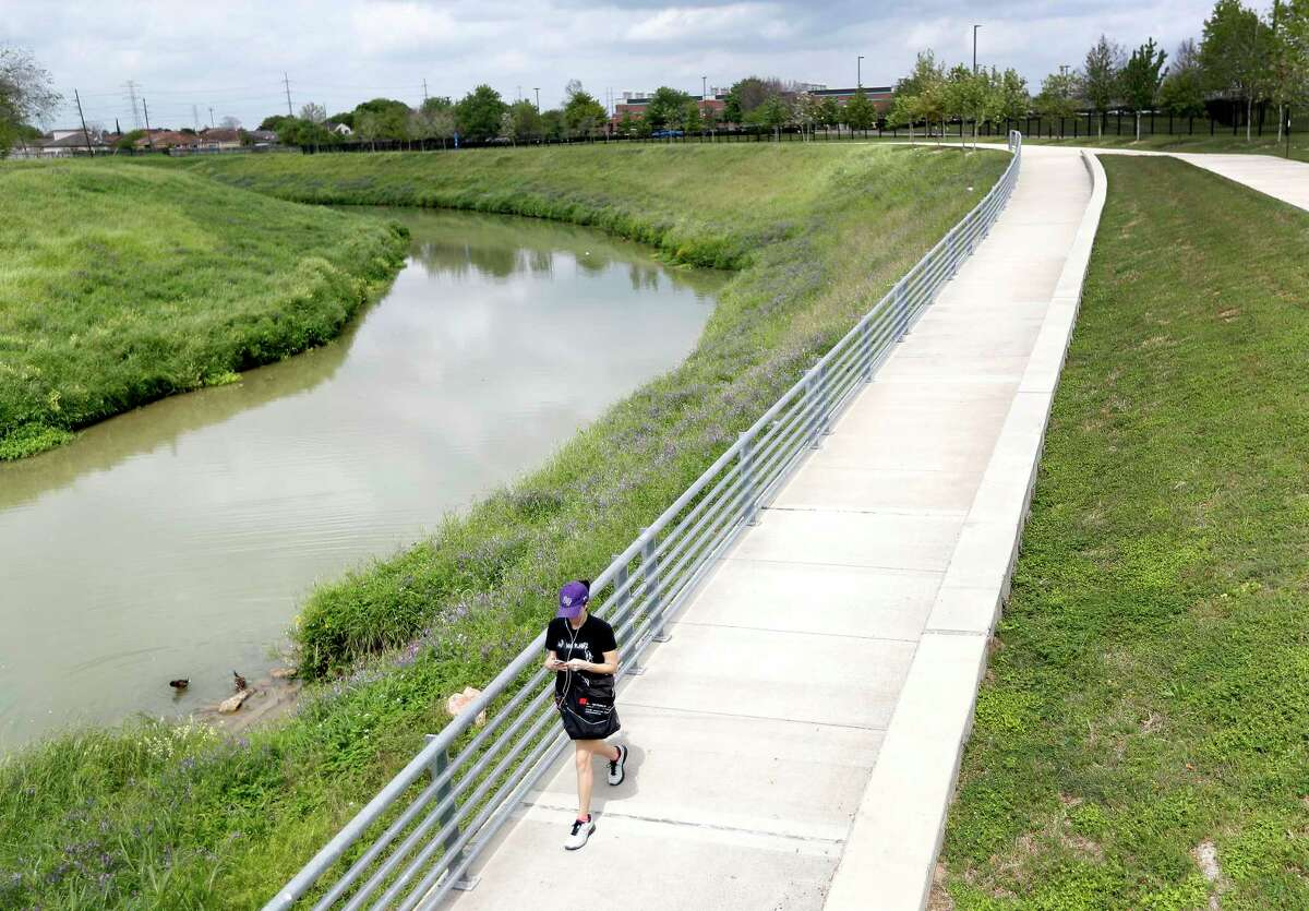 A woman walks near the Arthur Storey Park area of the Westchase District trail near Bellaire and the Sam Houston Tollway along Brays Bayou, in Houston on March 18, 2020. Some of the best trails in the Houston area for commuting aren't where you think they are. Westchase - viewed by some about as suburban as you can get, is the only place where Buffalo Bayou and Brays Bayou will actually connect by trail.