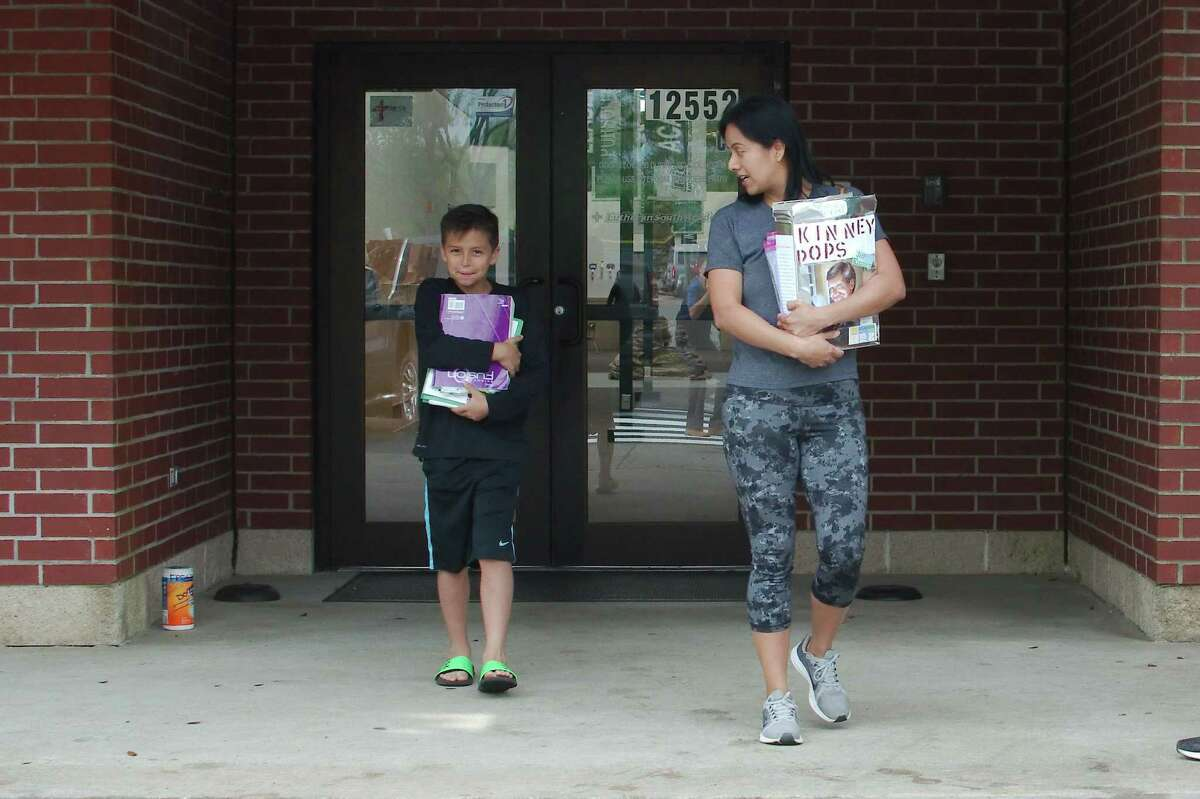 Lutheran South Academy third-grader Andrew Clark retrieves school supplies with his mother Brenda at the school as it moved to convert education activities online because of concerns about the novel coronavirus.