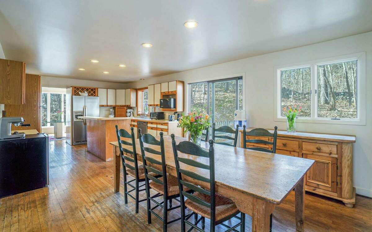 """The eat-in kitchen features a two-tiered center island, ample cabinetry, appliance """"garage,"""" built-in wine rack, and sliding doors to the sizable wood deck."""