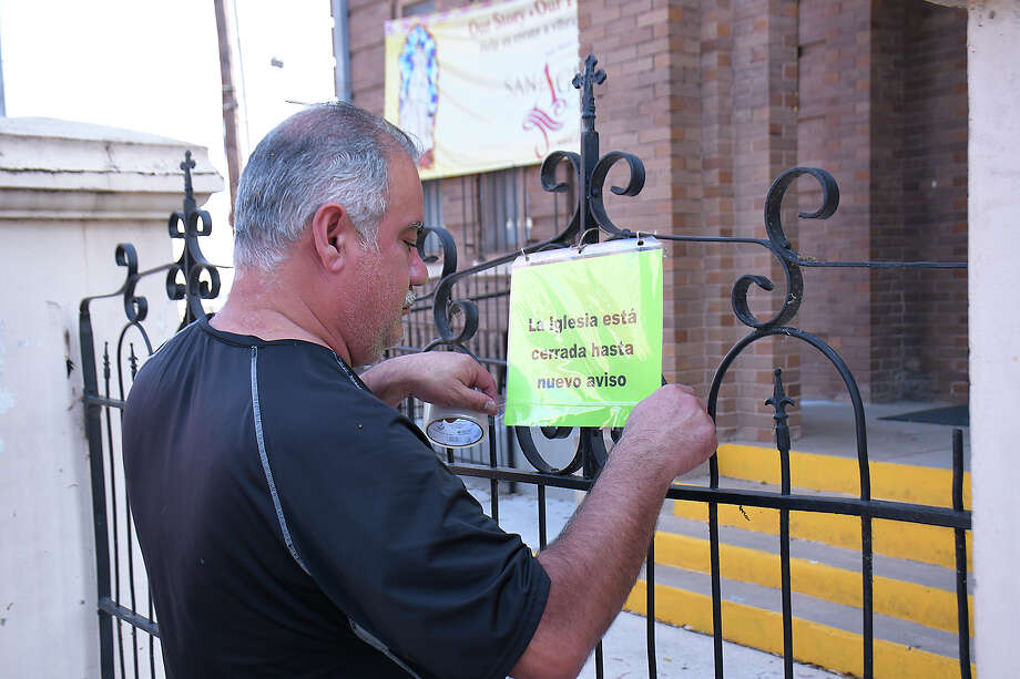An employee at San Agustin Cathedral posts a notice outside the church saying it will be closed until further notice, Thursday, March 19, 2020. The closure is in part because of the mandatory coronavirus lockdown approved by City Council. Photo: Cuate Santos/Laredo Morning Times