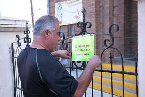 An employee at San Agustin Cathedral posts a notice outside the church saying it will be closed until further notice, Thursday, March 19, 2020. The closure is in part because of the mandatory coronavirus lockdown approved by City Council.