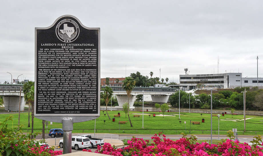 A view of a sign with the history of the Gateway to the Americas International Bridge, seen in the background, Friday, Mar. 20, 2020, after travel restrictions were announced at the U.S.-Mexico border amid concerns of COVID-19 Coronavirus spreading. Photo: Danny Zaragoza/Laredo Morning Times