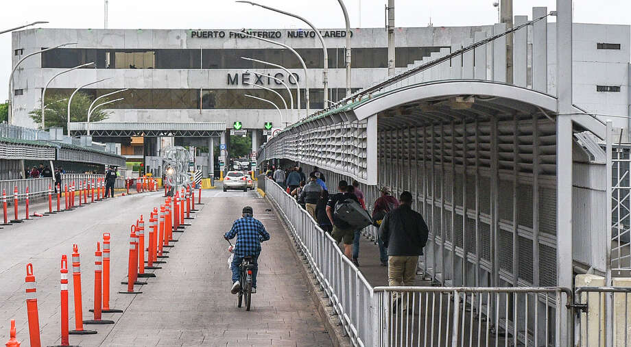 Pedestrians, motorists and cyclists cross the Gateway to the Americas International Bridge, Friday, Mar. 20, 2020, after travel restrictions were announced at the U.S.-Mexico border amid concerns of COVID-19 Coronavirus spreading. Photo: Danny Zaragoza/Laredo Morning Times
