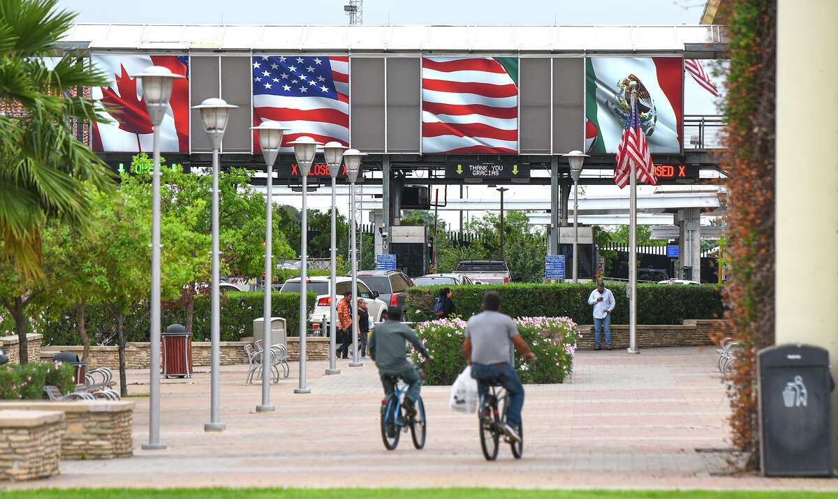 Pedestrians, motorists and cyclists head to the Gateway to the Americas International Bridge, Friday, Mar. 20, 2020, after travel restrictions were announced at the U.S.-Mexico border amid concerns of COVID-19 Coronavirus spreading.