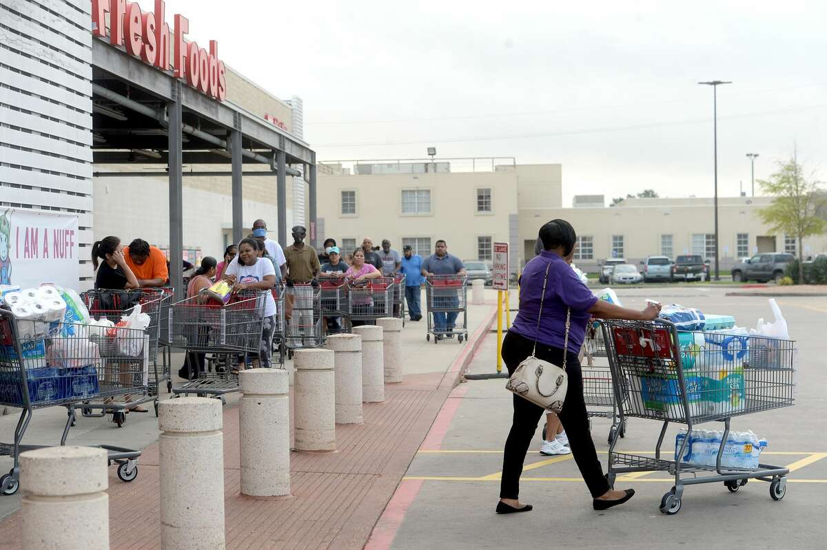 A line of shoppers await admittance outside the H-E-B store on College Street in Beaumont Thursday morning. Long lines gathering for store openings is becoming a morning routine, with shoppers hoping to get restocked items, especially paper products, cleaning supplies and non-perishables, before they quickly fly off the shelves. Photo taken Thursday, March 19, 2020 Kim Brent/The Enterprise