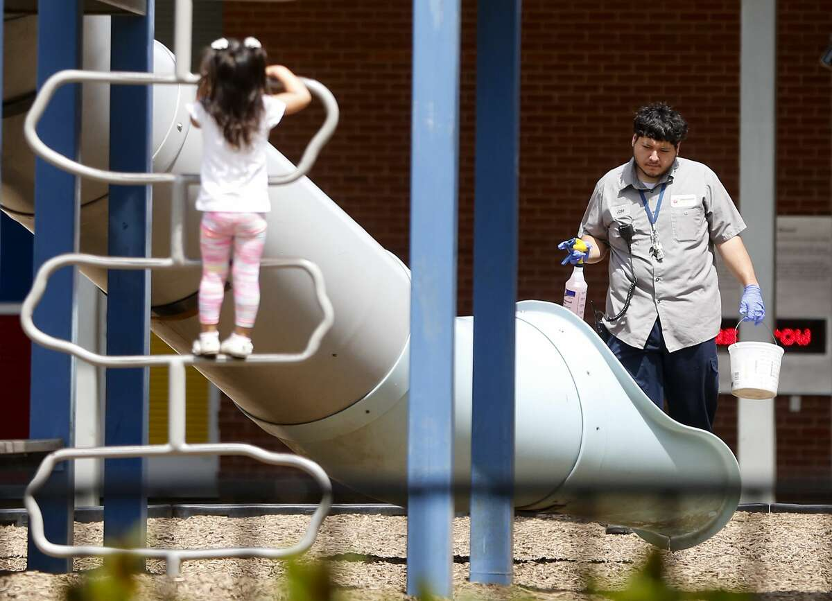 An employee for Discovery Green makes his way to the playground equipment with bleach and water in Houston on Thursday, March 19, 2020.