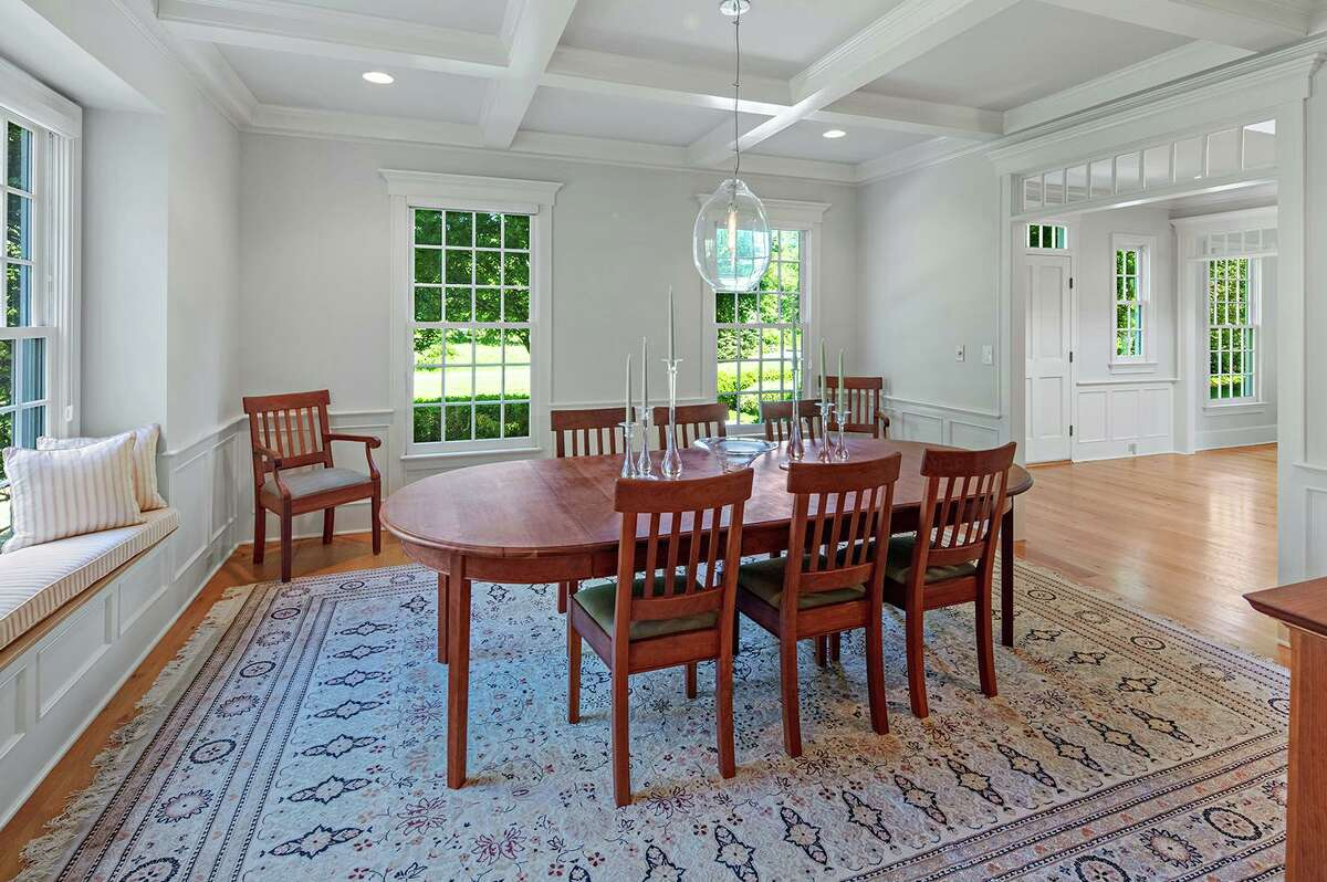 The formal dining room features a coffered ceiling and a built-in window seat.