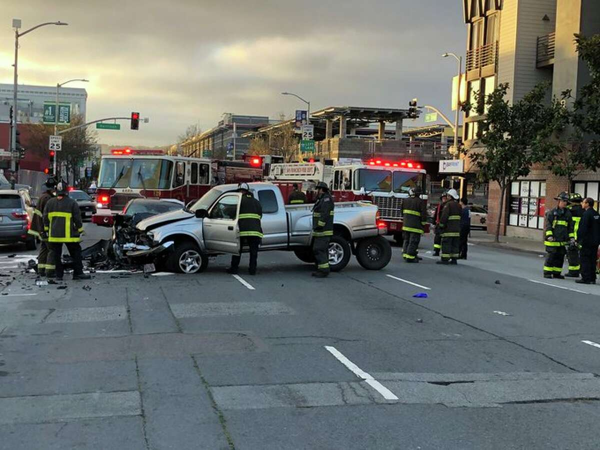 Emergency personnel respond Monday to a crash involving a pickup truck and a car in the area of 10th and Harrison streets in San Francisco.