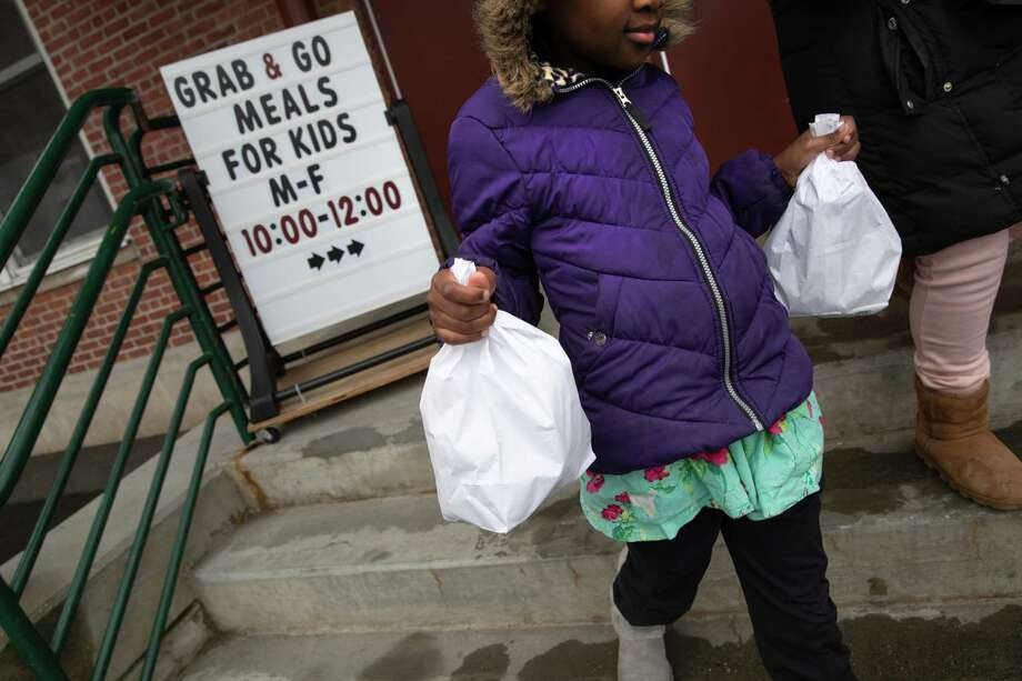 """STAMFORD, - MARCH 17: A student carries home bagged meals given out as part of Stamford Public Schools' """"Grab and Go Meals for Kids"""" program, which is part of the city's response to the coronavirus pandemic on March 17, 2020 in Stamford, Connecticut. Since public schools in Stamford closed last week to help slow the spread of COVID-19, the city is offering two bagged meals per child each day. Many low-income families count on school meals to feed their children.. (Photo by John Moore/Getty Images) Photo: John Moore / Getty Images / 2020 Getty Images"""