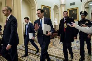 Treasury Secretary Steven Mnuchin, third from left, and White House Legislative Affairs Director Eric Ueland, left, walk to a meeting with Senate Minority Leader Sen. Chuck Schumer of N.Y. in his office on Capitol Hill, Monday, March 23, 2020, in Washington. The Senate is working to pass a coronavirus relief bill. (AP Photo/Andrew Harnik)