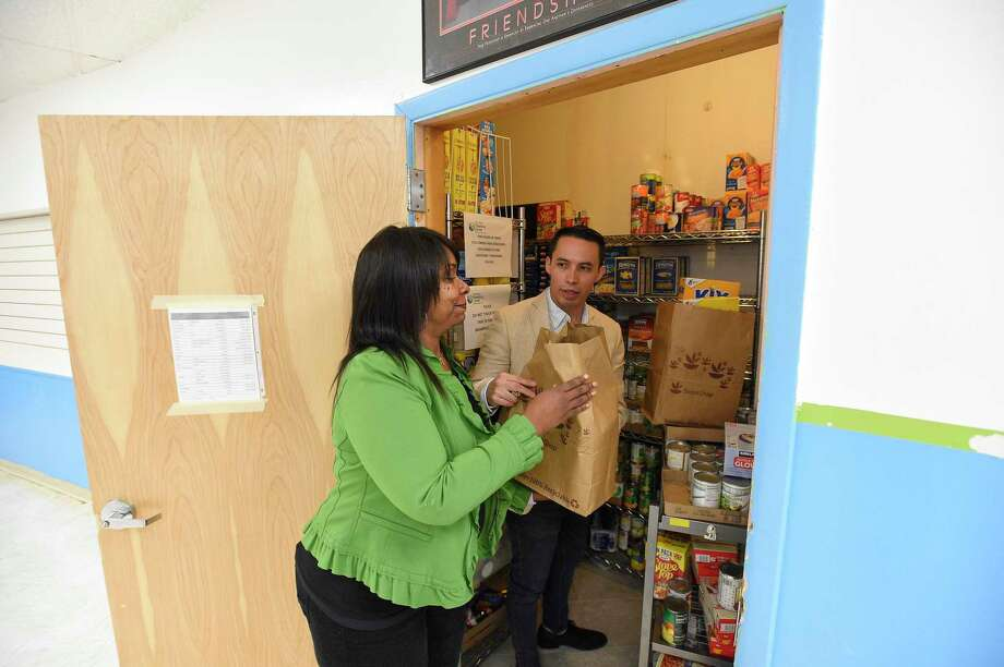 Luis Hernandez, Volunteer Program Manager for Saint Joseph Parenting Center and Rhonda Neal, Executive Director for Saint Joseph Parenting Center, accept a food donation from Rabbi Daniel Cohen of non perishable food items for the centers food pantry in Stamford, Conn. on March 19, 2020. Many food pantries throughout Fairfield County are bare as they struggle to serve the needs of their clients during ongoing Coronavirus crisis. Photo: Matthew Brown / Hearst Connecticut Media / Stamford Advocate