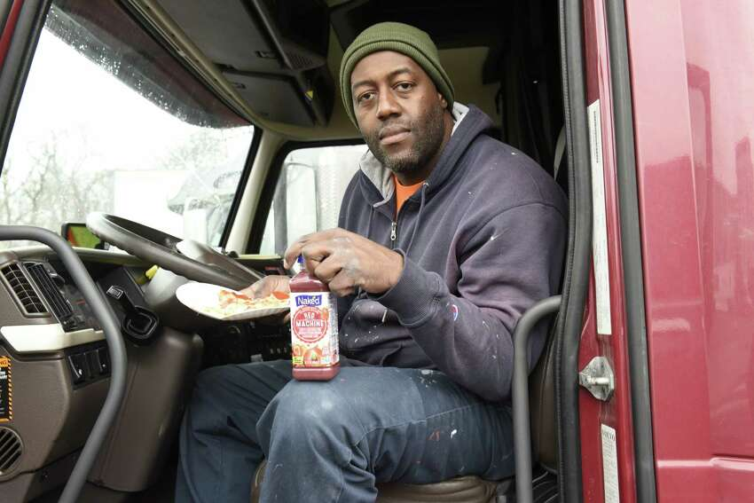 Robert Palmer of Albany is seen sitting in the cab of his truck with pizza and a drink at the Plaza 23 truck stop on Monday, March 23, 2020 in Albany, N.Y. Drivers are finding new hurdles as they try to deliver the goods, including limited opportunities for food and showers. (Lori Van Buren/Times Union)