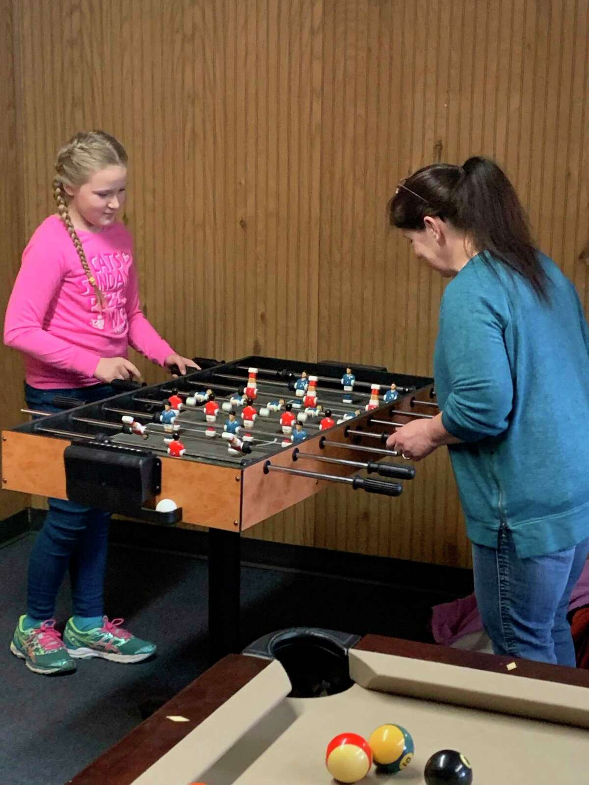 Chris Garcia plays some foosball with her daughter Jordon Smith during last week's activities at the Morley Community Center. (Courtesy photo/Morley Community Center)