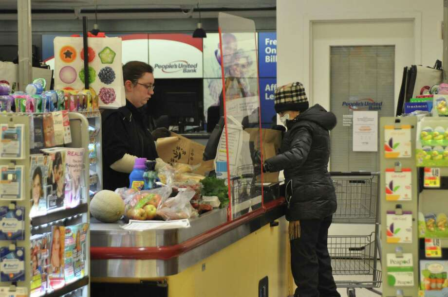 A masked senior citizen checked out with a supermarket workers who was behind a new protective plexiglass screen on Monday, March 22, in RIdgefield. Photo: Macklin Reid