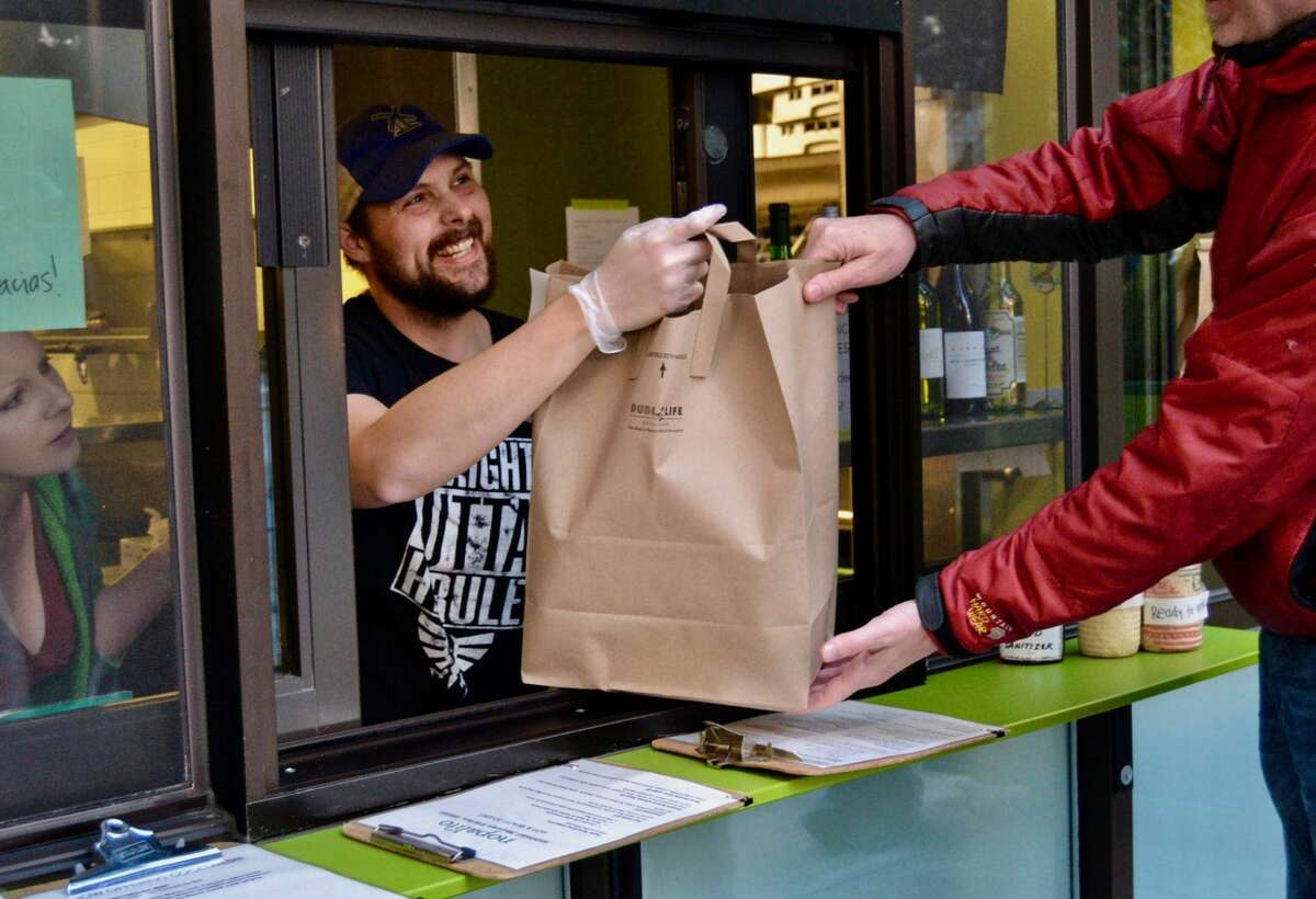 A cashier hands a to-go order to a customer at Nopalito on Broderick Street in San Francisco on Friday, March 20, 2020.