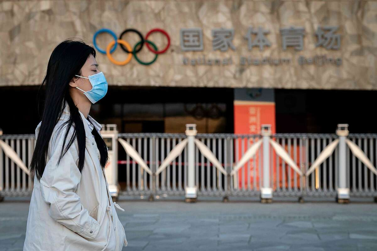 """A woman wearing a facemask as a preventive measure against the COVID-19 novel coronavirus walks at the Olympic park in Beijing on March 23, 2020. - World Athletics chief Sebastian Coe has called for the Tokyo Olympics to be postponed over the coronavirus pandemic as Canada pulled out of the Games and Japan's prime minister admitted a delay could be """"inevitable"""". (Photo by Nicolas ASFOURI / AFP) (Photo by NICOLAS ASFOURI/AFP via Getty Images)"""