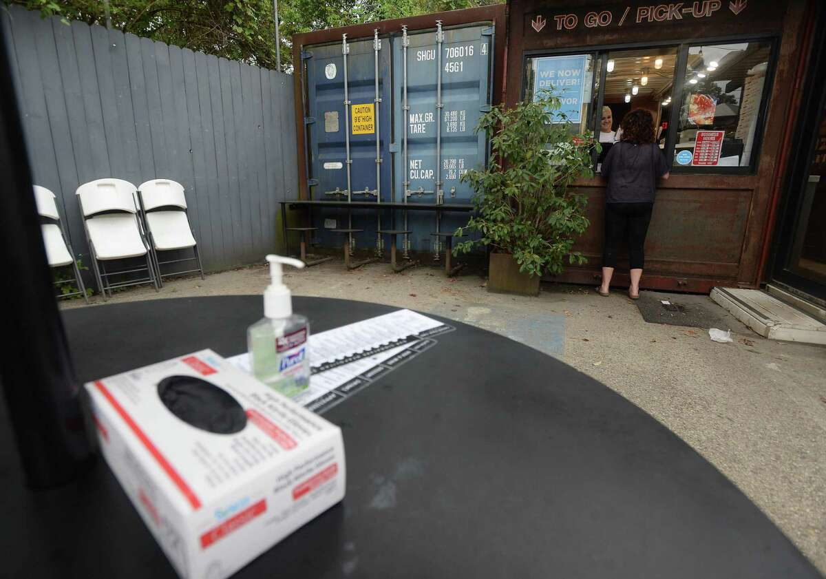 A box of gloves and bottle of hand sanitizer sit next to menus on a table outside Crown Pizza in Beaumont as worker Hailey Trest hands off orders to customers on the first day of area restaurant and bar closures.