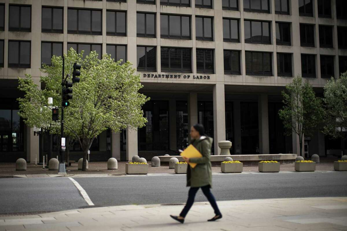A woman walks past the U.S. Department of Labor headquarters in Washington, D.C., U.S., on Wednesday, March 18, 2020. Treasury Secretary Steven Mnuchin raised the possibility with Republican senators that U.S. unemployment could rise to 20% without government intervention because of the impact of the coronavirus, according to people familiar with the matter.