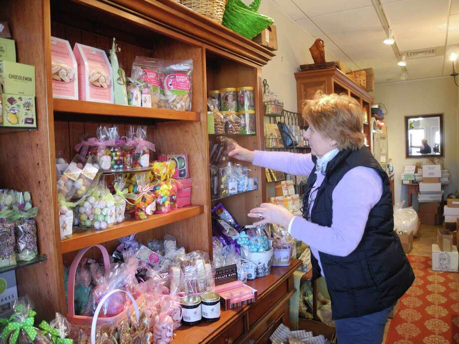 Nancy Saxe stocks the shelves at Sweet Pierre's in River Park Plaza, one of the businesses in town that's open. Photo: Jeannette Ross / Hearst Connecticut Media / Wilton Bulletin