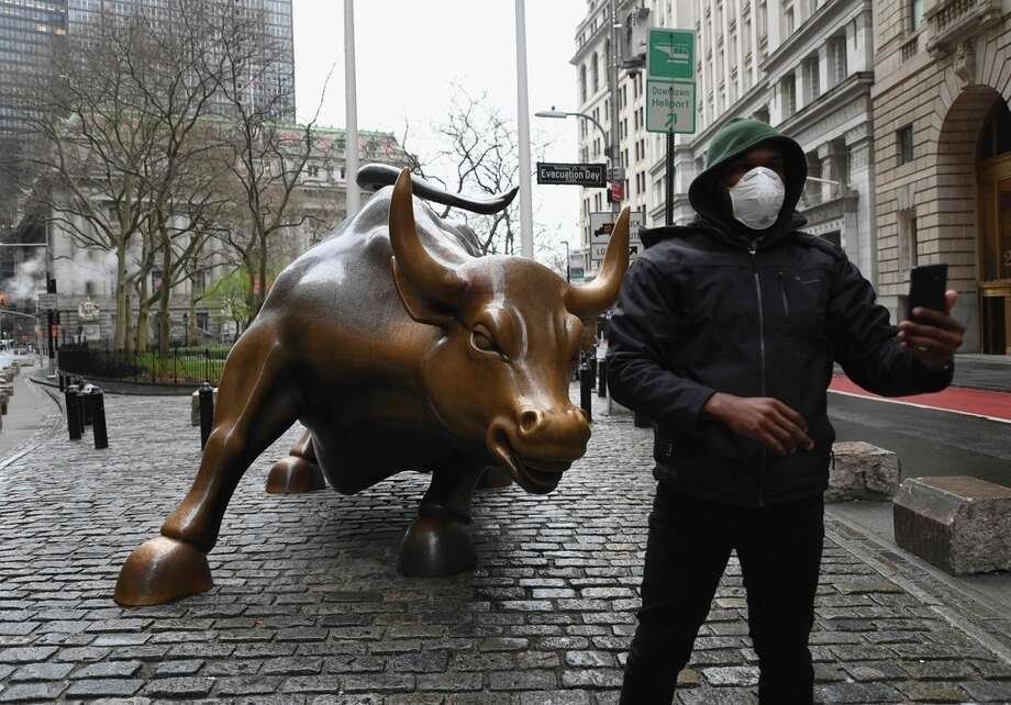 A man wearing a face mask takes a selfie at the Charging Bull statue on March 23, 2020  near the New Stock Exchange in New York City. - Wall Street fell early March 23, 2020 as Congress wrangled over a massive stimulus package while the Federal Reserve unveiled new emergency programs to boost the economy including with unlimited bond buying. About 45 minutes into trading, the Dow Jones Industrial Average was down 0.6 percent at 19,053.17, and the broad-based S&P 500 also fell 0.6 percent to 2,290.31 after regaining some ground lost just after the open. (Photo by Angela Weiss / AFP) Photo: ANGELA WEISS, Getty / AFP or licensors