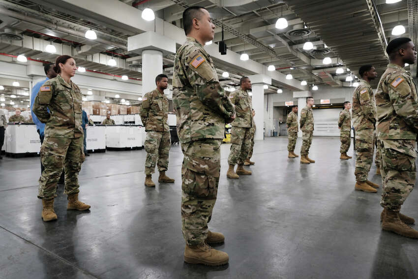 NEW YORK, NEW YORK - MARCH 23: Members of the National Guard listen as New York Governor Andrew Cuomo speaks to the media at the Javits Convention Center which is being turned into a hospital to help fight coronavirus cases on March 23, 2020 in New York City. The plan is part of his New York state request for assistance to the federal government for four field hospital sites and aid from the U.S. Army Corps of Engineers. New York has been one of the hardest hit states in the nation with over 10,000 cases of COVID-19.