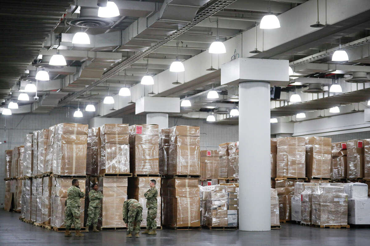 U.S. National Guard members stand beside crates of medical supplies at the Jacob Javits Center, Monday, March 23, 2020, in New York. New York City hospitals are just 10 days from running out of