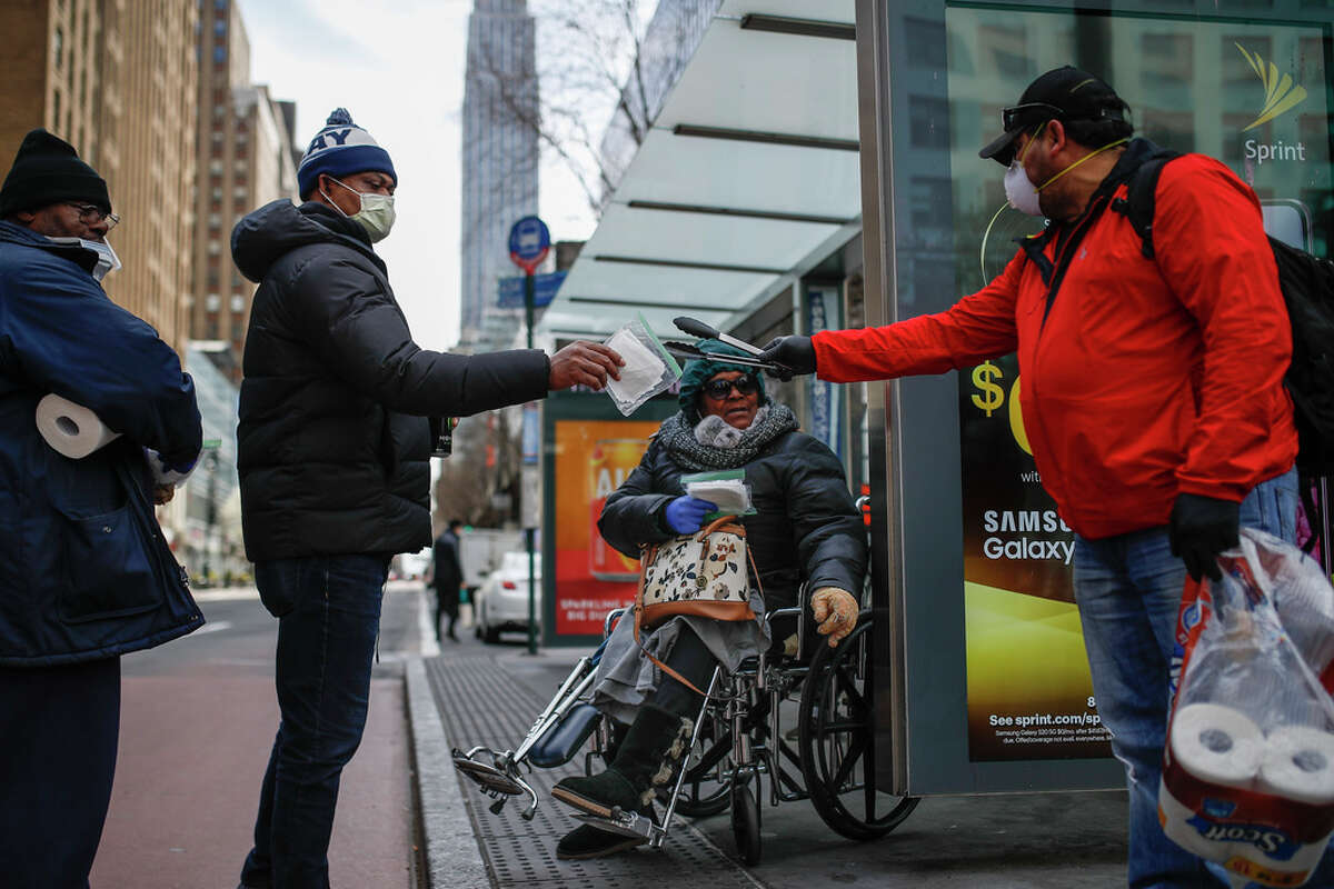 Felix Guzman, right, wears protective gloves and a mask due to COVID-19 concerns as he hands out disposable gloves and sanitizing wipes to people who are homeless on 34th Street, Saturday, March 21, 2020, in New York.