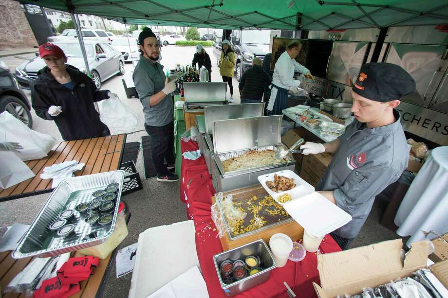 Toby Schwebel, manager B&B Butchers & Restaurant, dishes up a plate of food during a fund-raising pop up barbecue drive-thru at the restaurant on Saturday, March 21, 2020 in Houston. All funds raised during the event will go the restaurant's hourly employees, who have been put out of work during the restaurant shutdowns forced by the Coronavirus pandemic. Photo: Brett Coomer, Houston Chronicle / Staff Photographer / © 2020 Houston Chronicle