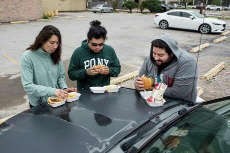 Arantxa Martinez, left, who works at Brennan's of Houston, Cristian Juarez, sous chef at Traveler's Table, and Robert Cantu, chef at Post Oak Grill, eat sandwiches given out by workers from Killen's BBQ on the hood of a car on Saturday, March 21, 2020 in Houston. Killen's BBQ handed out complimentary sandwiches and chips to members of the hospitality industry affected by coronavirus-related shutdowns in a pop up drive-thru at 101 Heights Blvd. In a post on Killen's BBQ Facebook page that they hope to keep using their resources and manpower to help feed workers until the restaurant closings are lifted.