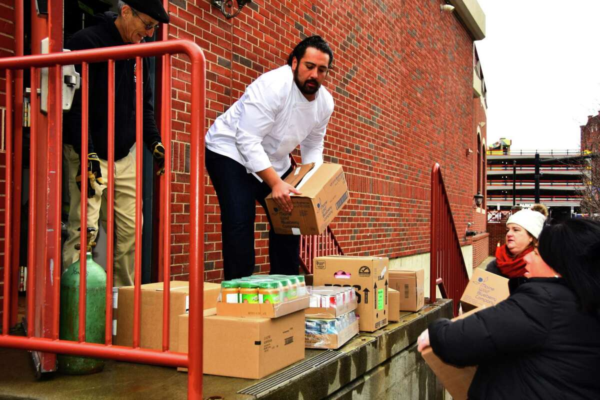Donated food is brought into Yono's restaurant in Albany by, from left, Bob Baker of the Regional Food Bank of Northeastern, Dominick Purnomo of Yono's and food bank employees Joslyn McArdle and Caitlyn Krug, on Monday, March 23, 2020.