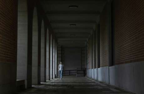 """Jacob Hermann, the assistant director of the Center for Academic and Professional Communications at Rice University, walks near Fondren Library on Thursday, March 12, 2020, at the Rice University in Houston. """"Everything is pretty much in overhaul mode right now,"""" Hermann said of the center's operations."""