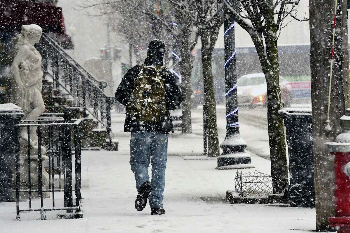 A pedestrian walks down a sidewalk on Lark St. in the snow on Monday, March 23, 2020 in Albany, N.Y. UAlbany is getting grant money in 2020 to use artificial intelligence to predict snowstorms. (Lori Van Buren/Times Union) ORG XMIT: j=032420_weather
