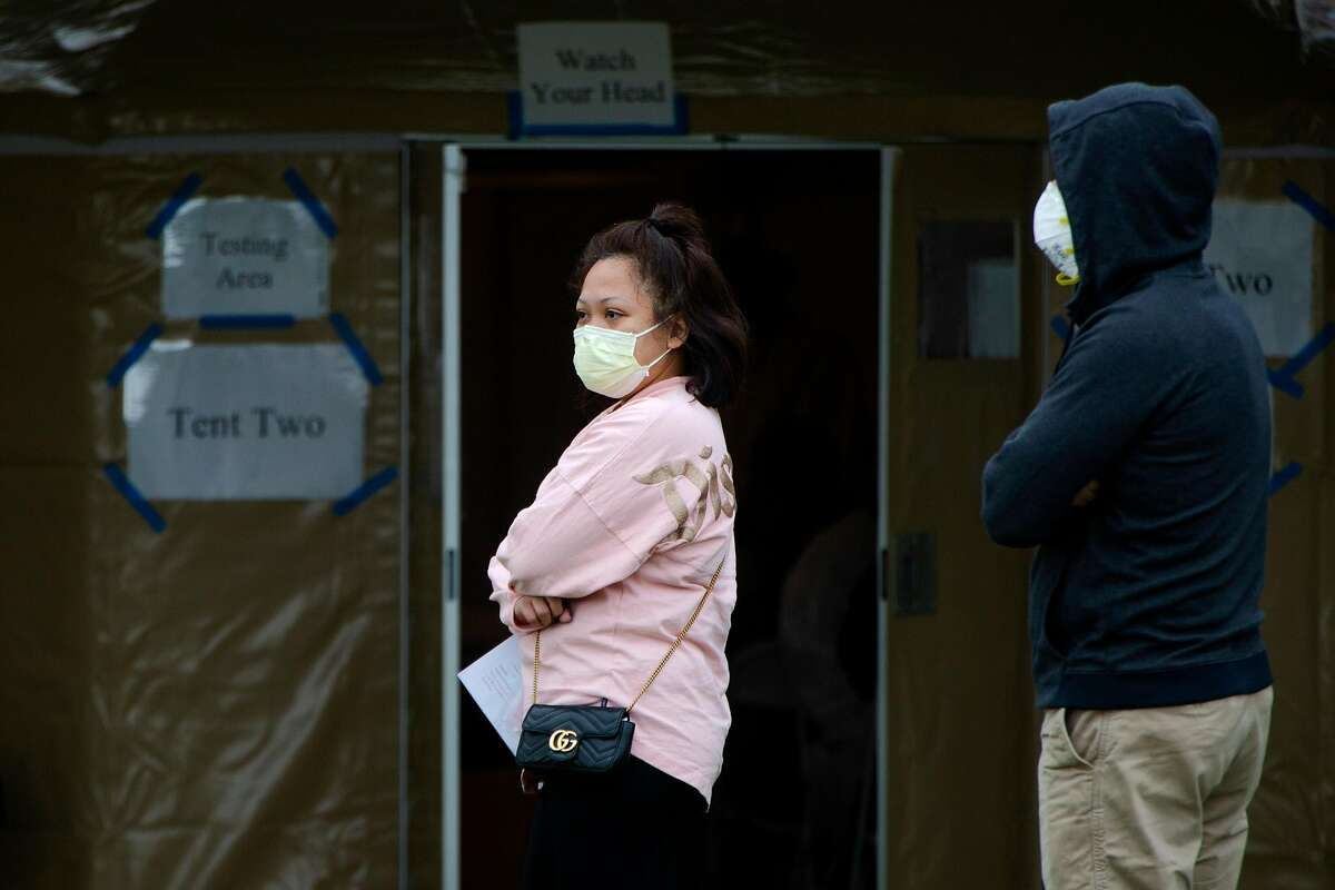 A woman waits in the cold outside of a testing tent at Haywards Fire Station #7 on Monday, March 23, 2020. The new Covid-19 testing location has been set up to help relieve pressure from hospitals. The site will be free and open for those who are sick, first responders and health-care workers.