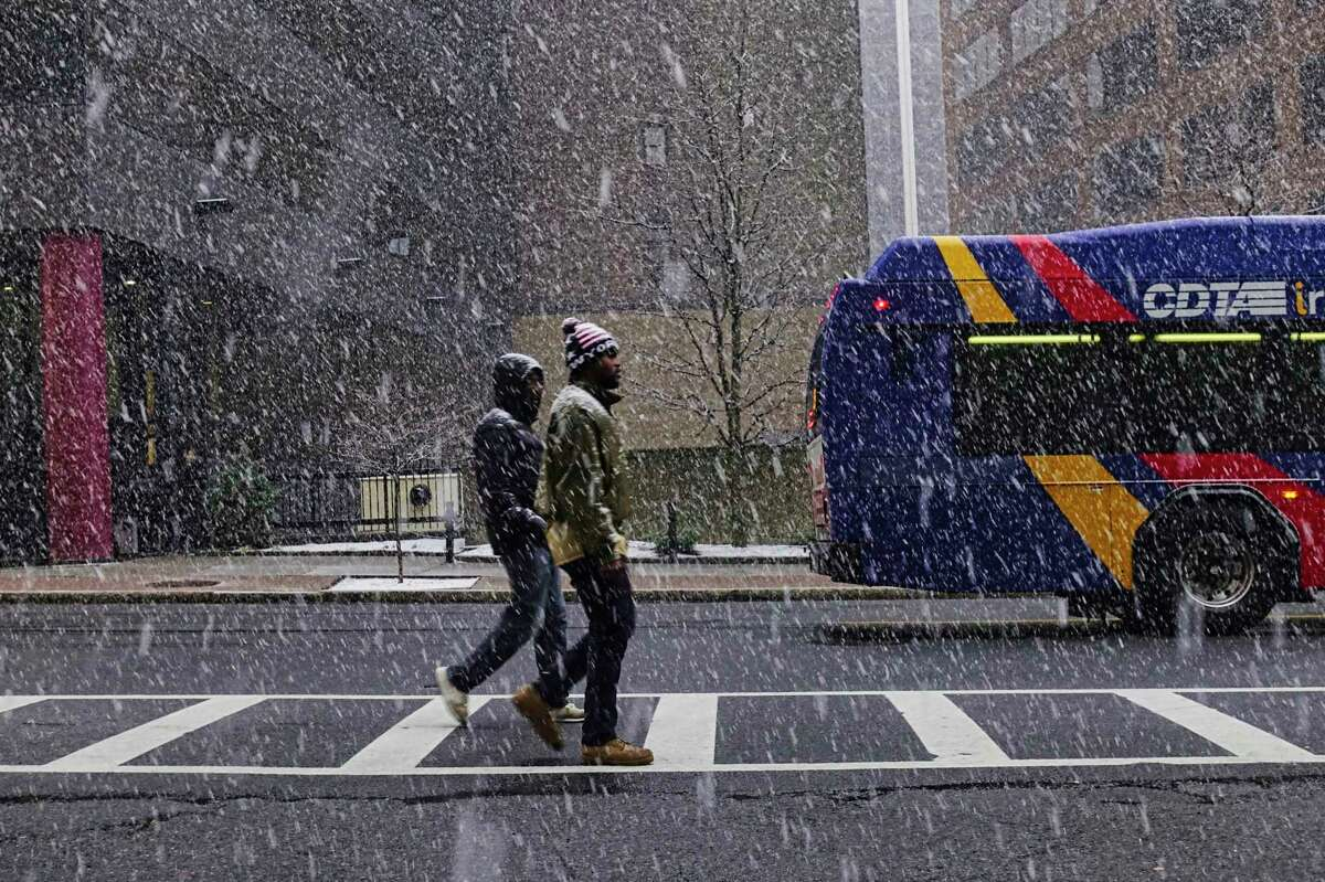Snow hit outlying parts of the Capital Region and Vermont overnight. In this photograph, people make their way down South Pearl Street as snow falls on Monday, March 23, 2020, in Albany, N.Y. (Paul Buckowski/Times Union)