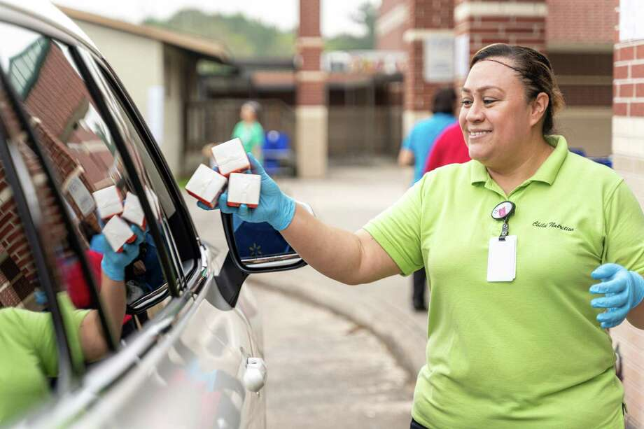 Mary Jimenez, Spring ISD Child Nutrition employee, hands out free curbside take-home meal items at Claughton Middle School for district students whose schools were closed the week of March 16, 2020. Photo: Courtesy Of Spring ISD, Web Specialist & Photographer / Spring Independent School District
