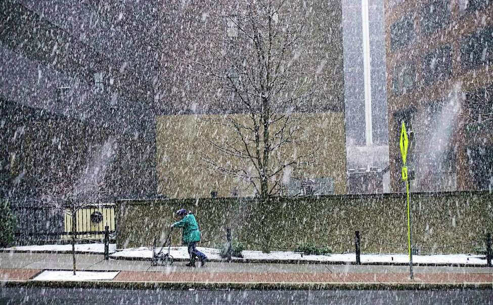 Warmth on Tuesday should melt at least some of what fell on us Monday. In this photograph, a man makes his way up South Pearl Street as snow falls on Monday, March 23, 2020, in Albany, N.Y. (Paul Buckowski/Times Union)