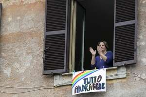 """In this photo taken on Saturday, March 14, 2020, a woman claps her hands next to a banner reading """"Everything will be alright"""", in Rome. Families around the world are placing rainbows in their windows to symbolize hope and unity.(Roberto Monaldo/LaPresse via AP)"""