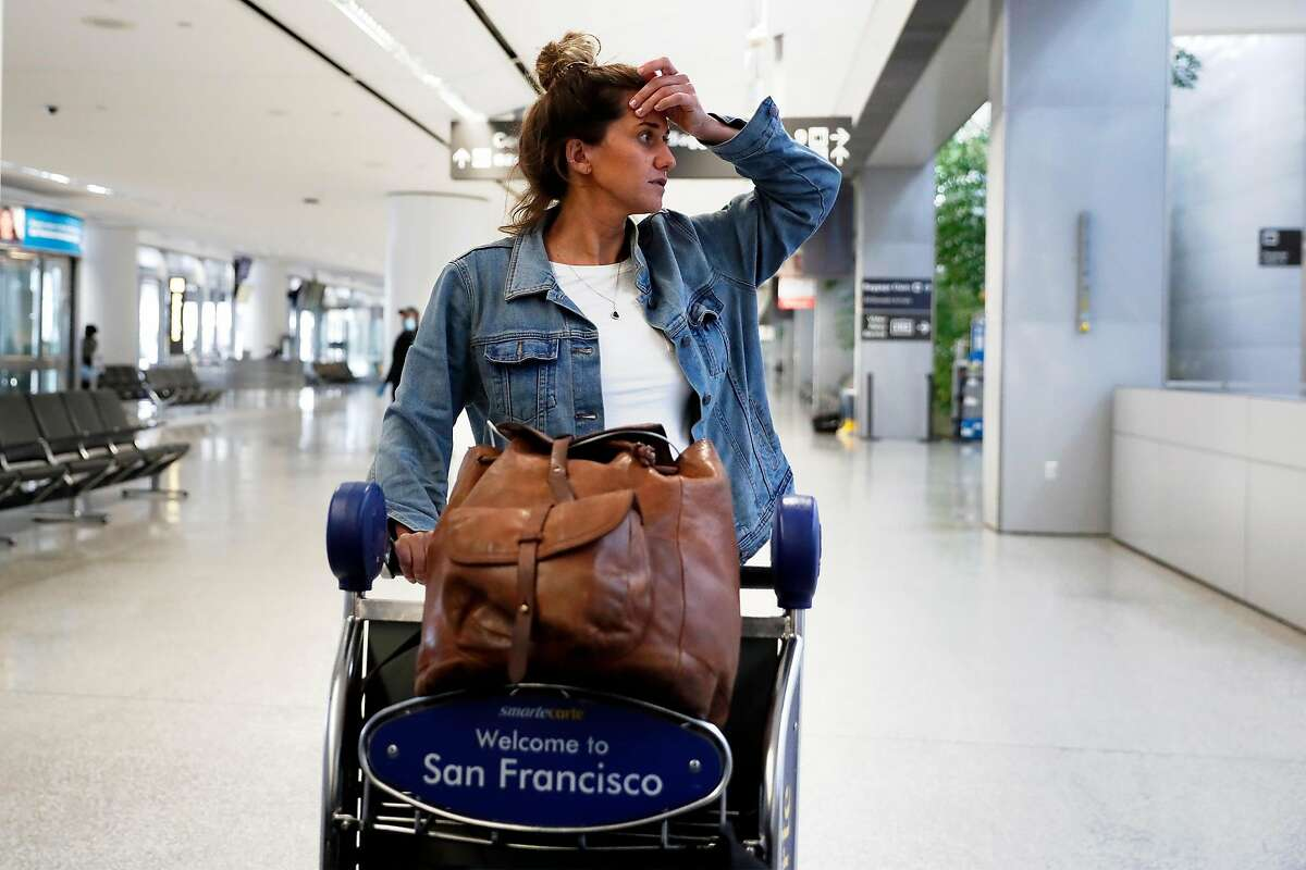 After arriving from Bali, Amanda Forth looks for directions to ride sharing pick up location in SFO International Terminal in San Francisco, Calif., on Monday, March 23, 2020. Forth closed down her jewelry store and returned to the US at the urging of her grandparents.