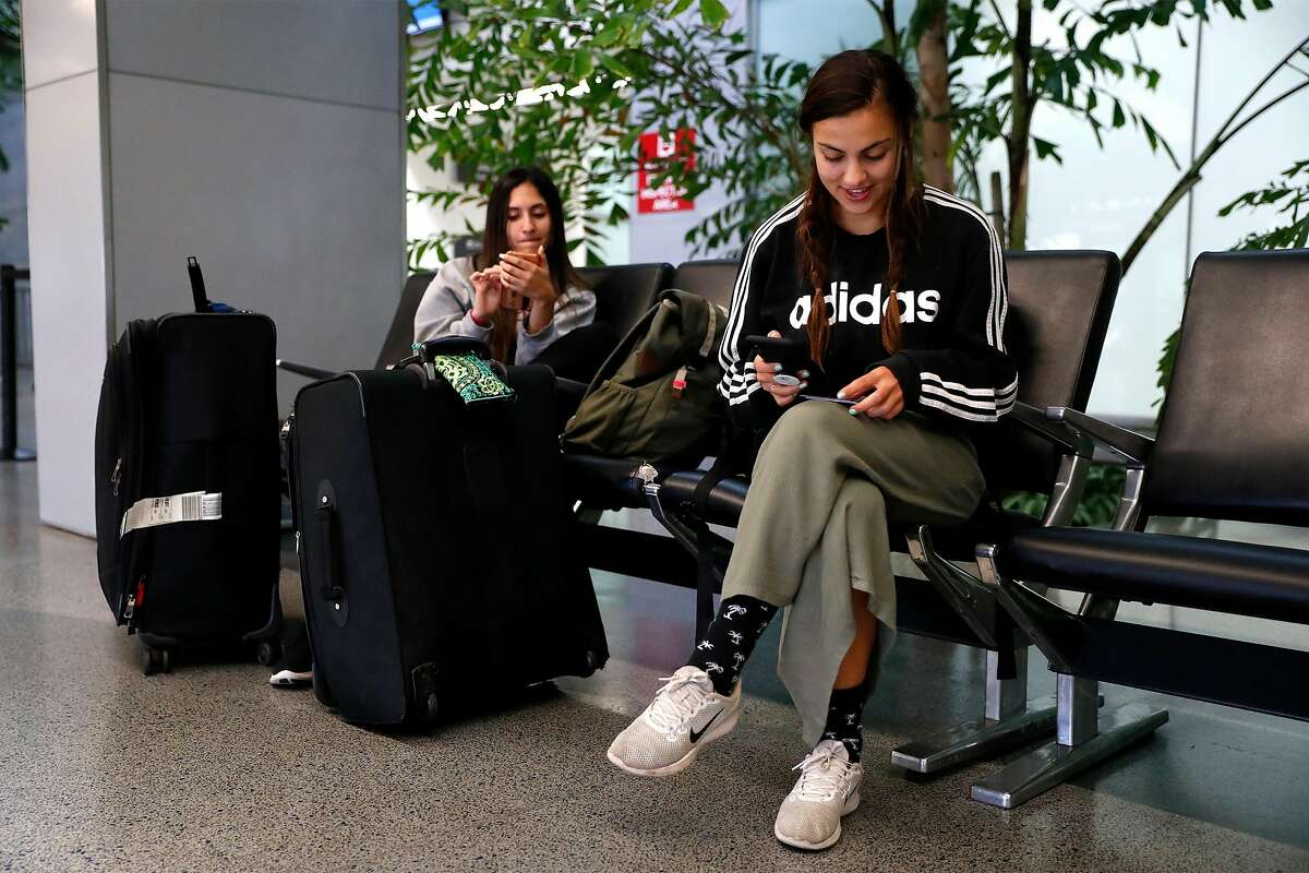 After returning from Bali, Hilay Farooq and her cousin, Shay Arghandiwal, both of San Ramon, arrange rides at SFO International Terminal in San Francisco, Calif., on Monday, March 23, 2020.