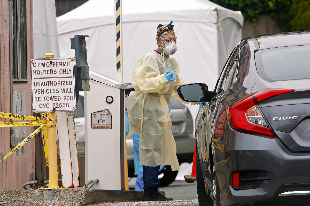 Medical staff work at a Coronavirus testing site at a parking lot at the CPMC Sutter Health California campus on Monday, March 23, 2020 in San Francisco, Calif. The Coronavirus testing site at a parking lot at the CPMC Sutter Health California Campus parking lot is currently a testing site for shared network of medical professionals including Brown and Toland network physicians and CPMC Sutter Health healthcare workers within San Francisco.