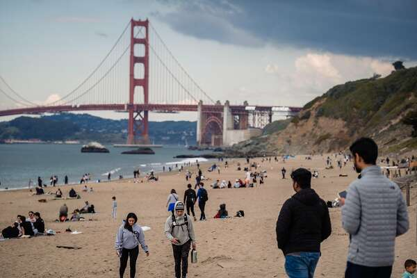 People gather on Baker Beach on this the 5th day of the city wide shelter in place order in San Francisco, Calif. on Saturday, March 21, 2020.