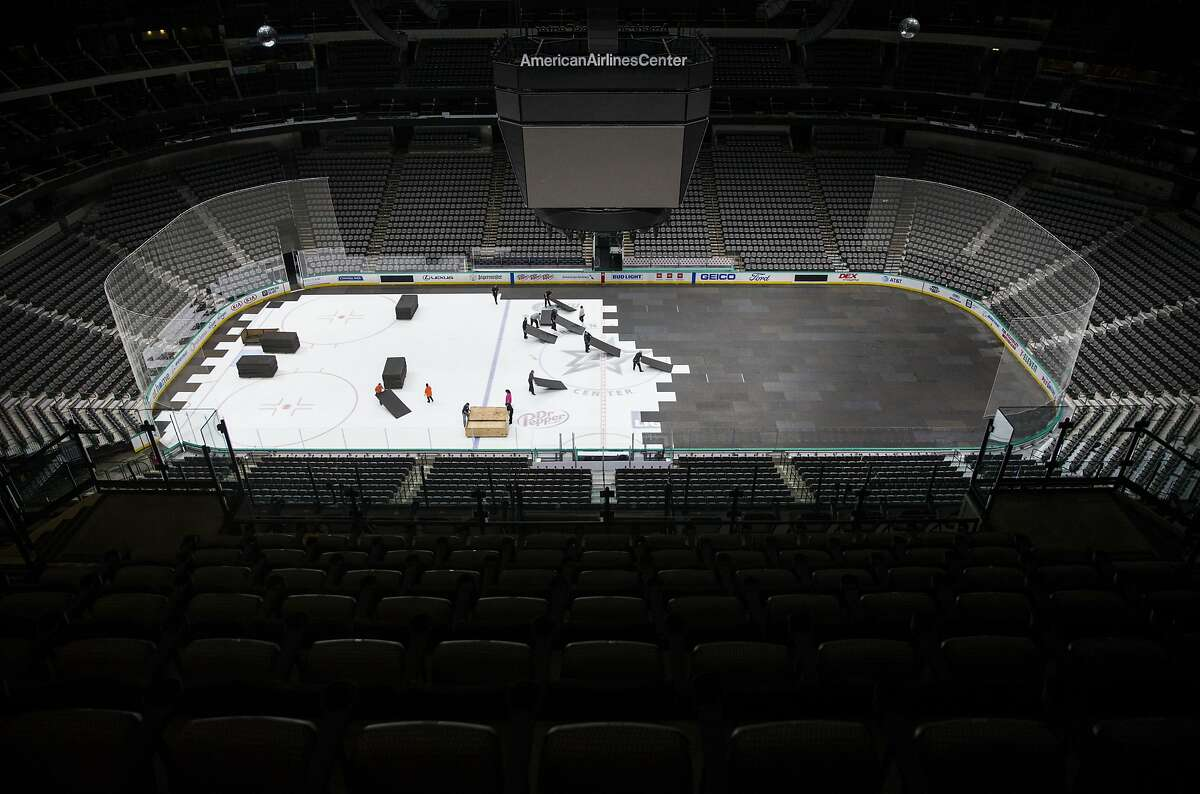 Crews cover the ice at American Airlines Center in Dallas, home of the Dallas Stars hockey team, after the NHL season was put on hold due to coronavirus, Thursday, March 12, 2020. (Ashley Landis/The Dallas Morning News via AP)