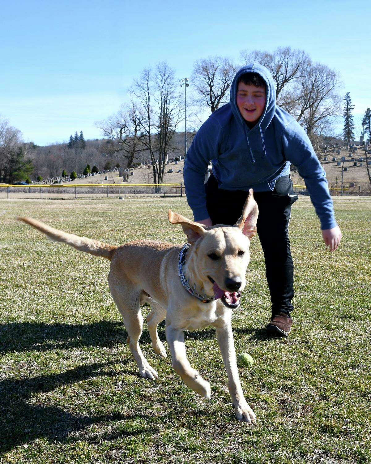 Winsted resident Nicholas Grinvalsky plays with his yellow lab, Tucker.