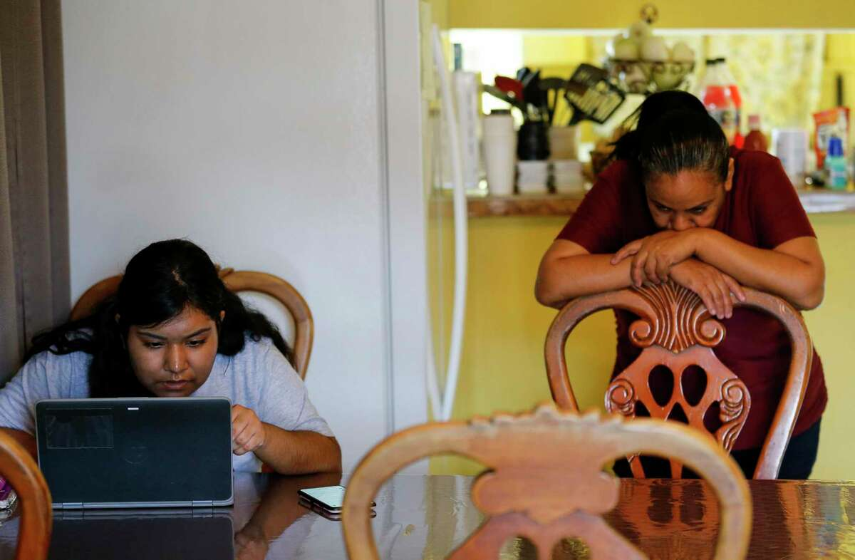Jacqueline Ricalday, 18, left, works on scholarships in her dining room Thursday, March 19, 2020, in Houston. Ricalday, a senior at Northside High School, doesn't know when school and her internship at Texas Children's Hospital will resume, after both were halted due to the new coronavirus pandemic. She has also seen her hours at Marble Slab Creamery slashed because of the virus.