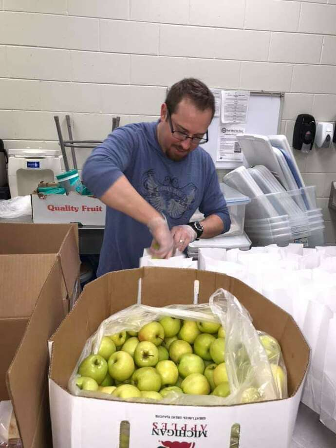 Apples are put in the lunch bags for the students taking part in the school breakfast and lunch program, which is helping to make sure children get fed during the coronavirus break from school. Photo: Courtesy Photo
