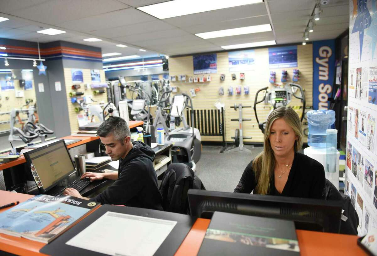 Carlos Lopez and Lisa Ripley work at Gym Source in Greenwich on Monday. Gym Source is among businesses deemed non-essential by the state and will be closed starting Tuesday, despite having a higher volume of customers purchasing home gym equipment to use during the coronavirus quarantine. Although the store will be closed, customers can still shop online for home delivery.