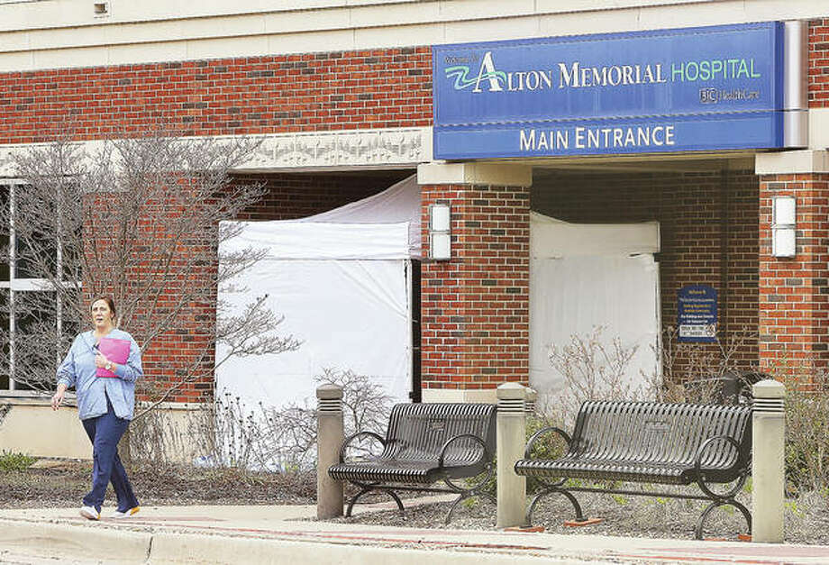 A woman walks out of the main public entrance to Alton Memorial Hospital Monday where a tent-like structure has been erected. Structures have been put up at the Emergency entrance to the hospital as well, apparently to screen visitors for signs of the COVID-19 virus. OSF St. Anthony's Hospital in Alton put visitation restrictions into place Monday and Alton Memorial Hospital plans to do the same starting Tuesday.